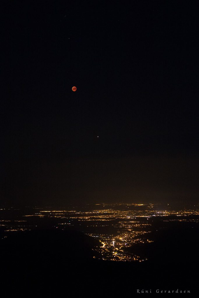 Lunar eclipse above a city