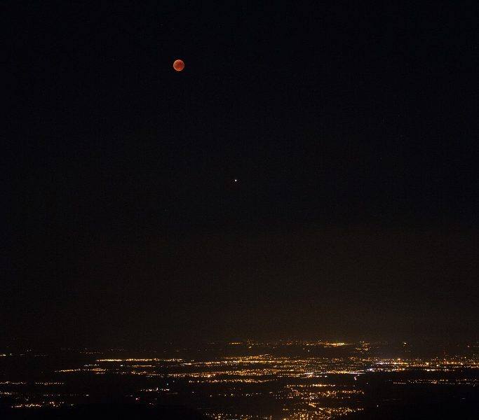 Lunar eclipse above a city